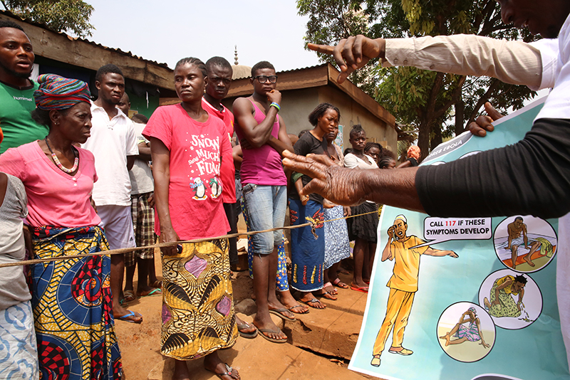 UNICEF coordinators and volunteers using illustrations to help educate people about the Ebola outbreak on March 12, 2015 in Freetown, Sierra Leone. These families are being held in a quarantine because one of their neighbors contracted Ebola.