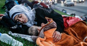 UNDP Turkey/Huseyin Sari/GFSD Golcuk. A homeless mother sleeping with her baby on a grass patch near highway.